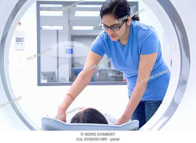Technician with patient in CT scanner