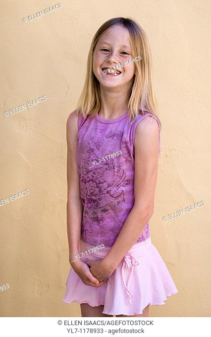 Nine-year-old blonde girl in a pink top and purple skirt sticking her tongue between her teeth and laughing