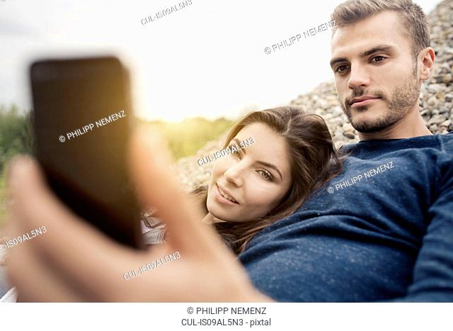 Attractive young couple posing for selfie on smartphone