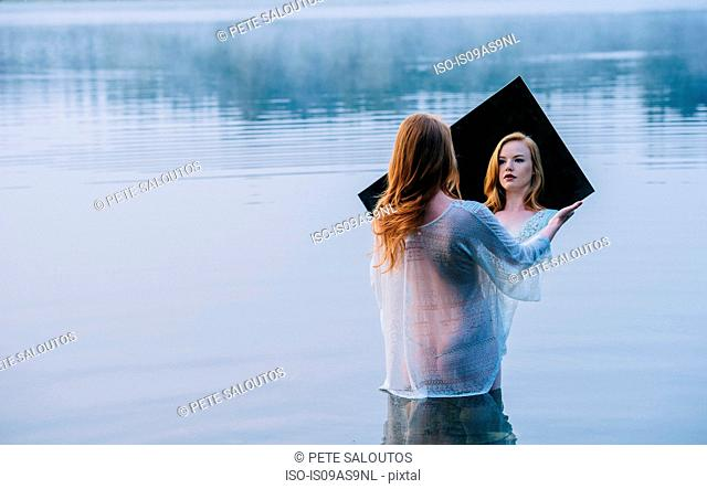 Rear view of young woman standing in lake holding mirror looking at reflection