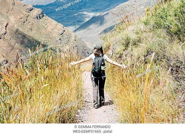 Peru, Valle Sagrado, woman hiking on the way to the Incan ruins of Pisac Archaeological Complex