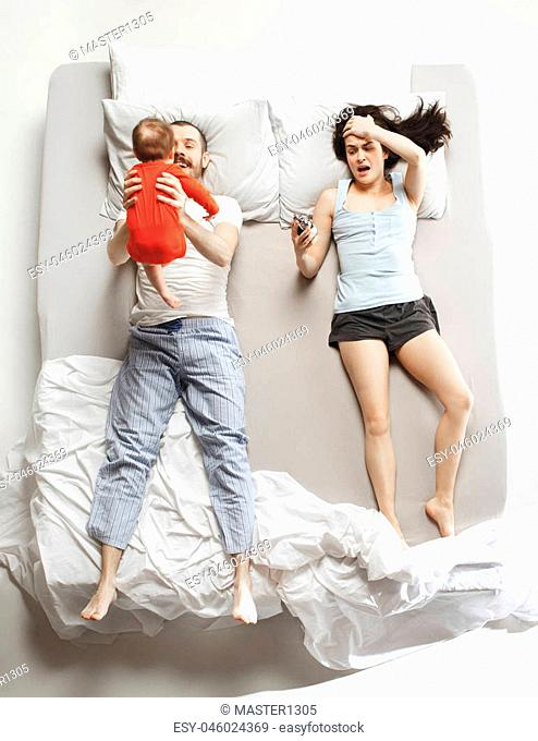 Top view of happy funny family with one newborn child in bedroom. Enjoying being together. Happy family in bed. Top view. Emotions concept