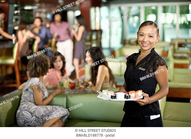 Waitress serving sushi in restaurant