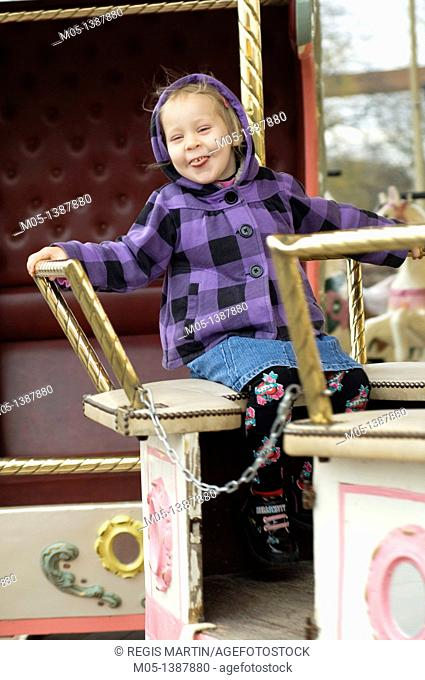 4 years old girl on a carousel in Paris, France