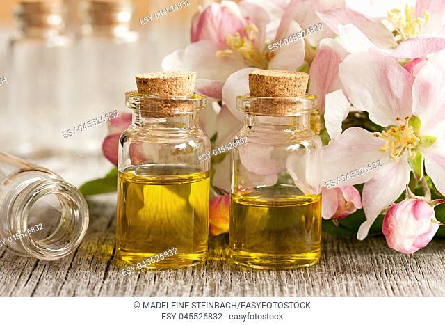 Two bottles of essential oil with apple blossoms in the background