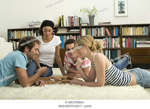 Four young people on floor, playing Backgammon
