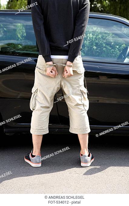 A man standing next to a car wearing handcuffs