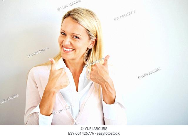 Cheerful young casual businesswoman showing goodluck sign with both hand against grey background