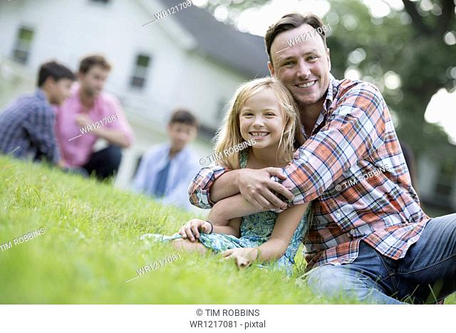 A father and daughter at a summer party, sitting on the grass