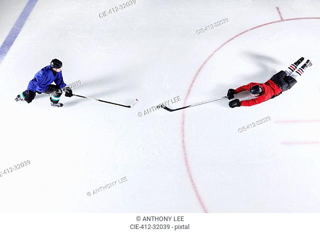 Overhead view hockey players diving for puck on ice