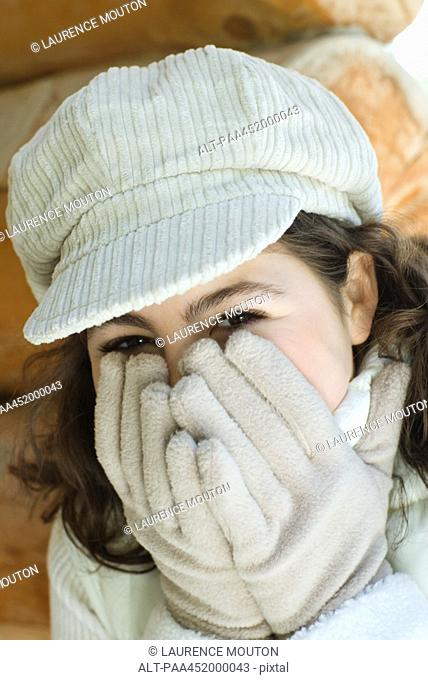 Teenage girl holding gloved hands over mouth, close-up