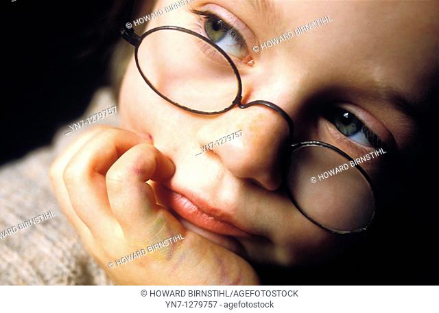 child with glasses looking pensive