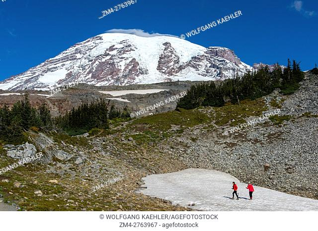 View from the Skyline Trail of Mount Rainier with hikers on a snow field in Mt. Rainier National Park in Washington State, USA