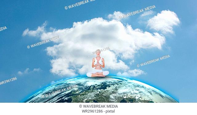 Fit woman meditating on earth against sky