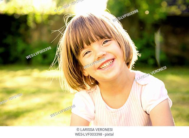 Portrait of smiling little girl in a garden