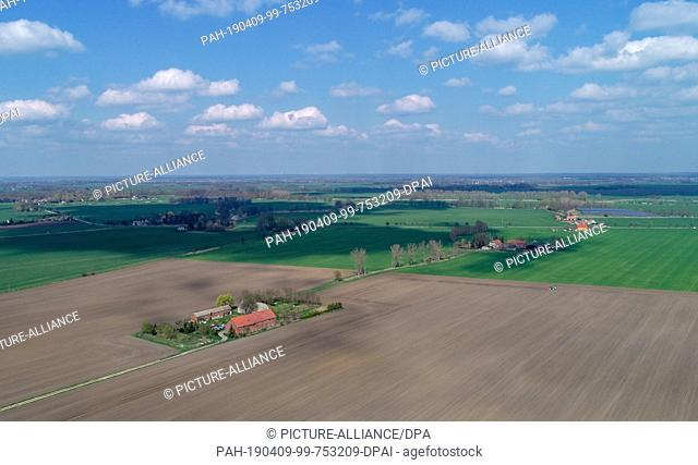 09 April 2019, Brandenburg, Golzow: Individual Loose farmsteads between the wide fields in the Oderbruch (aerial photograph with a drone)