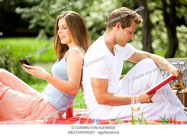Couple with cell phone and book on picnic blanket in park
