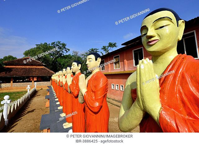 Figures of Buddhist monks in front of a monastery, near Sigiriya, Central Province, Sri Lanka