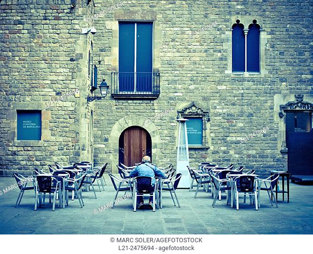 Barcelona City History Museum facade. Tables and chairs at square. Plaça del Rei, Gothic quarter, Barcelona, Catalonia, Spain