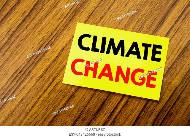 Hand writing text caption inspiration showing Climate Change. Business concept for Global Planet Warming written on sticky note paper on wooden keyboard...