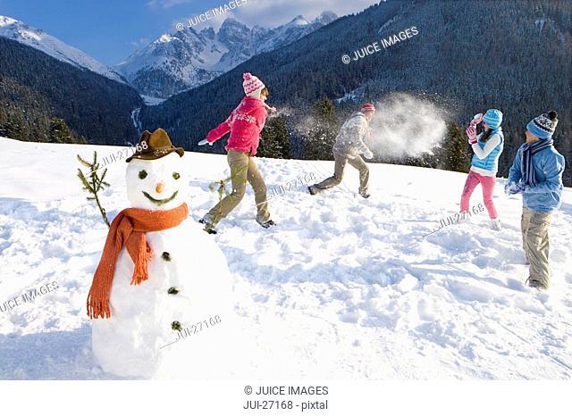 Family having snowball fight on ski slope near snowman