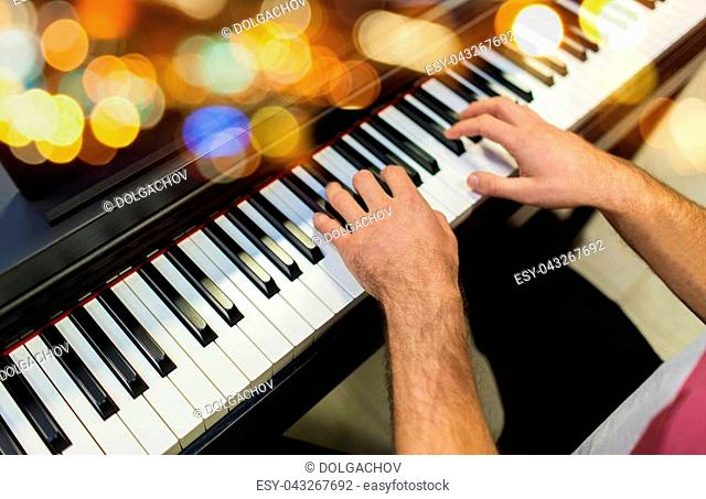 music, people and instruments concept - close up of male hands playing piano over lights