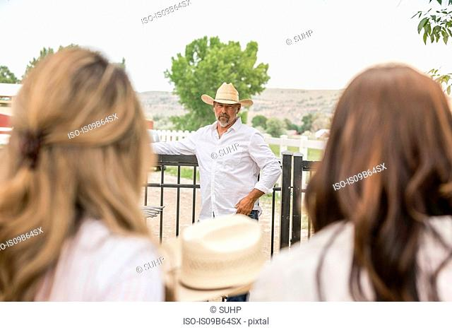 Over shoulder view of mature man in cowboy hat leaning on ranch gate, Bridger, Montana, USA