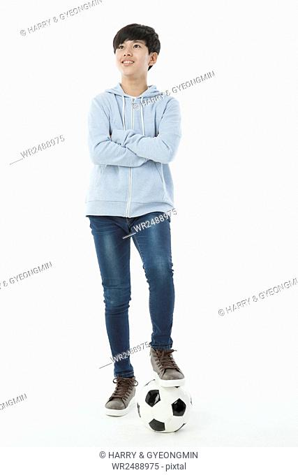 Smiling teenager boy standing with a soccer ball folding arms looking up