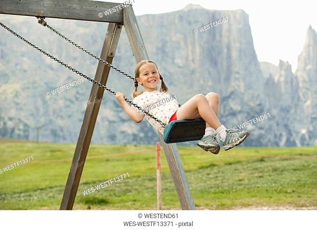 Italy, Seiseralm, Girl 6-7 sitting on swing, portrait