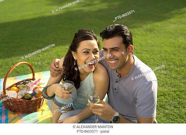 Man and woman sitting on picnic blanket laughing