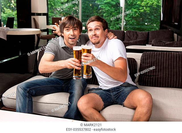 Two football fans celebrating victory of their football team. Looking happy
