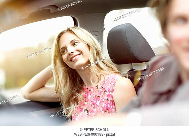 Portrait of smiling blond woman sitting on passenger seat in a car