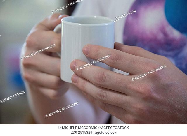 Close up of a man's hands holding his cup