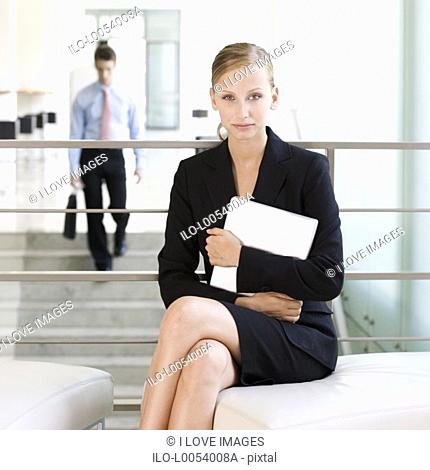 A businesswoman waiting with a laptop
