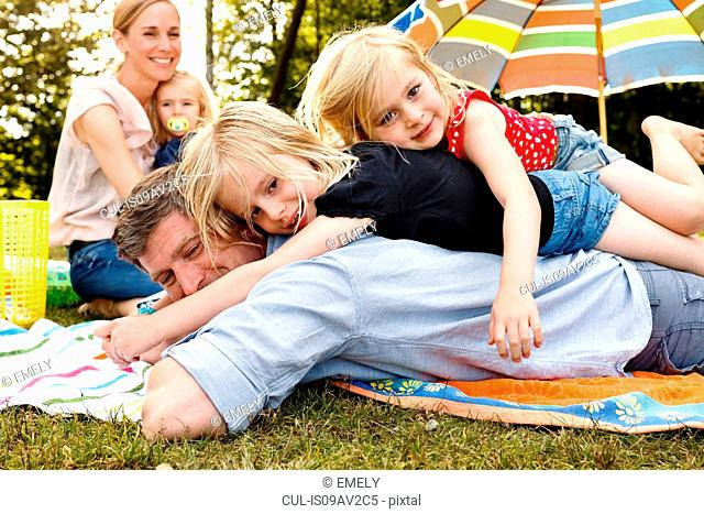 Two daughters lying on top of father at family picnic in park