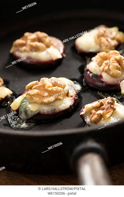 Roasted beetroots with chevre goat cheese and walnuts in a pan
