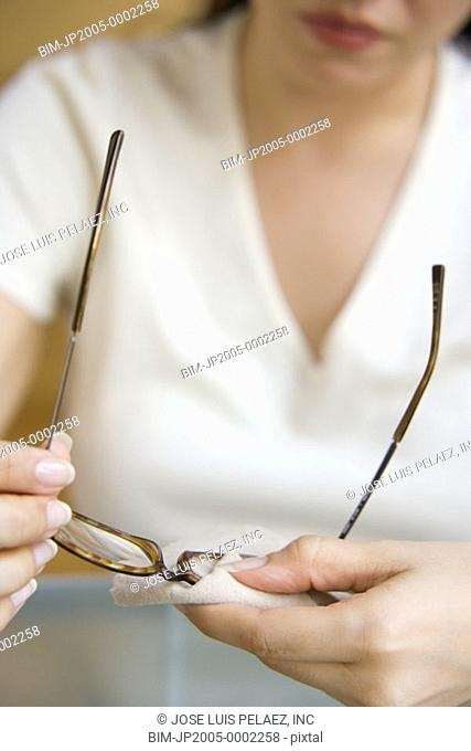 Woman polishing her glasses