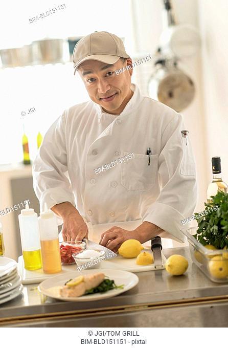 Korean chef slicing food in kitchen