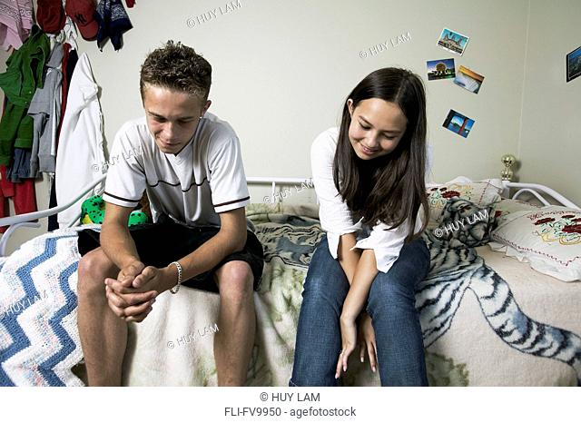 Teenage Boy and Girl Sitting on Bed