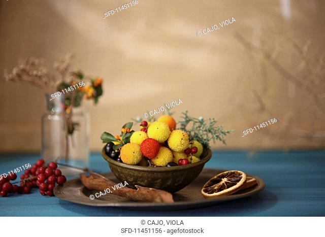 Various winter fruits in a metal bowl
