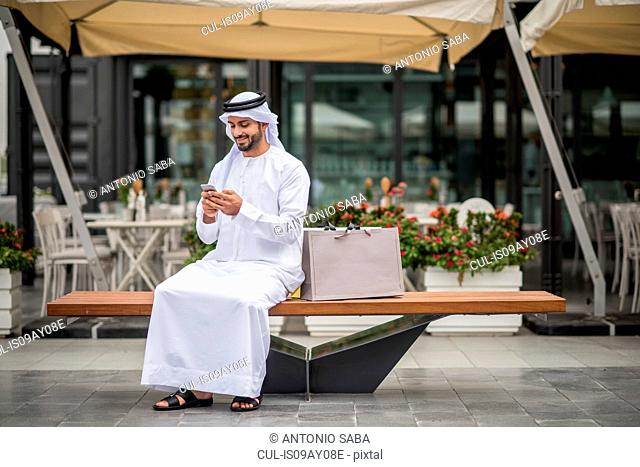 Male shopper wearing traditional middle eastern clothing sitting on bench reading smartphone text, Dubai, United Arab Emirates