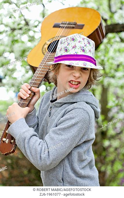 Boy with an acoustic guitar playing outdoor in the garden