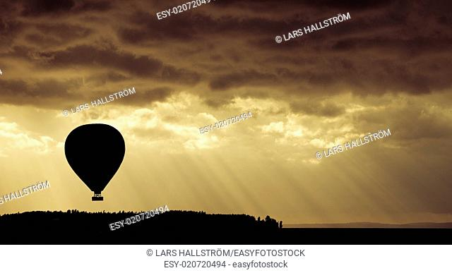 Beautiful nature scene with silhouette of hot air balloon flying at sunset