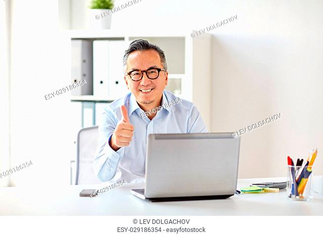 business, people and technology concept - happy smiling businessman in eyeglasses with laptop computer showing thumbs up at office