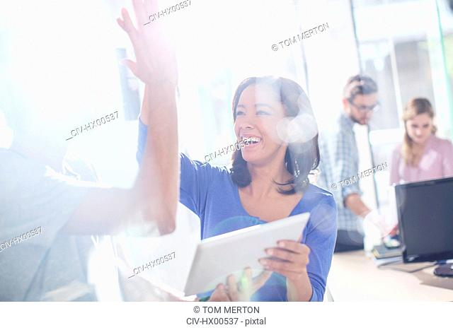 Creative business people high fiving with digital tablet