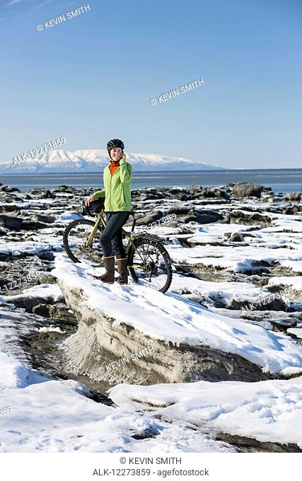 Young woman with her bicycle talks on a cell phone while standing on frozen ice chunks along the Tony Knowles Coastal Trail, Anchorage, Southcentral Alaska