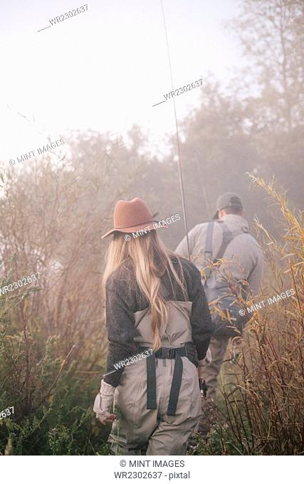 A couple, a man and woman walking along a riverbank with fishing gear
