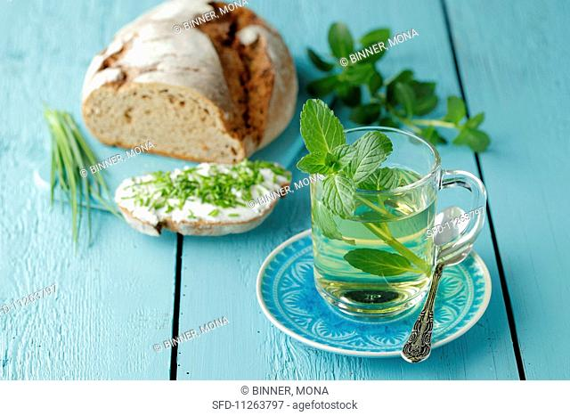 A glass of mint tea next to a loaf of bread with cream cheese and chives