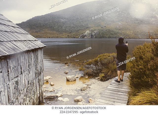Young Tasmanian hiking tourist taking photo on the Dove Lake walking track when traveling Australia