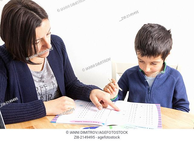 Mother tutoring young boy at home